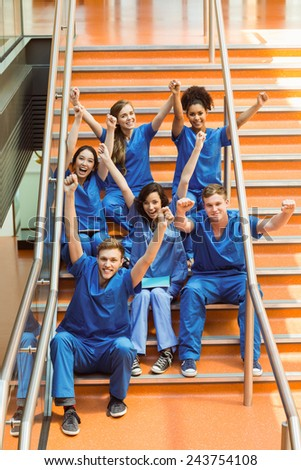 Medical students cheering on the steps at the university - stock photo
