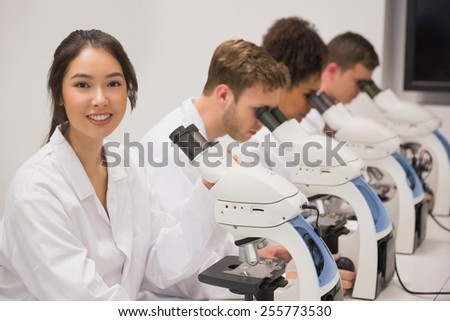 Medical students working with microscope at the university - stock photo