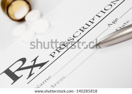 Medical stuff - prescription, pills and pen on table - stock photo