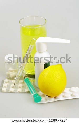 Medical supplies, tablets and capsules, spray throat and drink, lemon - stock photo