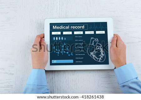 Medical tablet in doctor hands on light background - stock photo