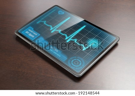 Medical tablet PC on table showing cardiogram on display. - stock photo
