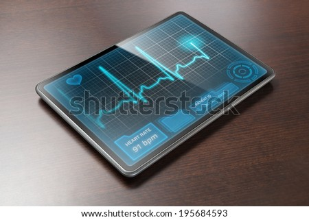 Medical tablet PC on table showing cardiogram on display