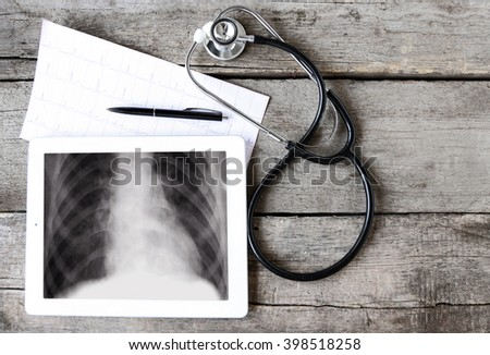 Medical tablet with stethoscope on table background - stock photo