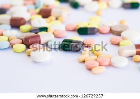 Medical tablets and pills on gray background.