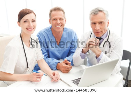 Medical team at work. Cheerful medical team sitting together at the table and looking at camera - stock photo