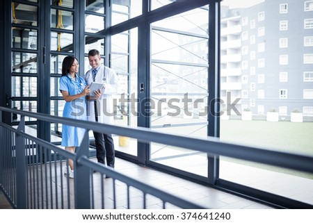 Medical team discussing some results in hallway - stock photo