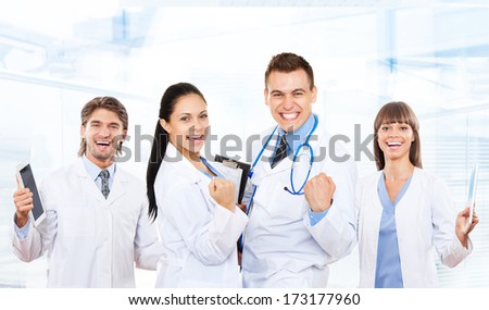 medical team doctor happy smile excited, hold fist yes hand gesture wear white coat with stethoscope, group of people celebrating in hospital