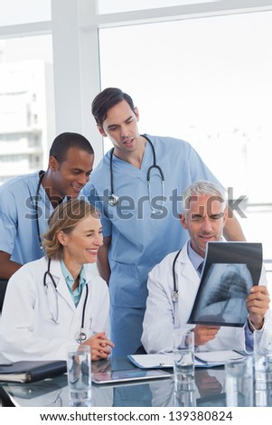 Medical team examining radiography in office - stock photo