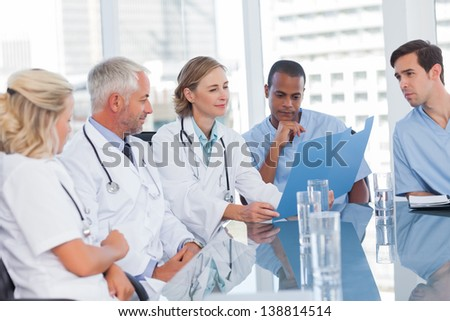 Medical team looking at a file in office - stock photo