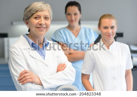 Medical team of three professional woman at dental surgery portrait - stock photo