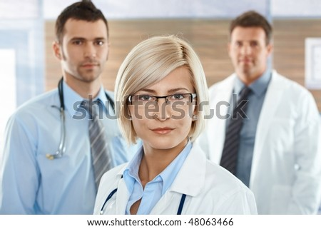 Medical team on hospital corridor female doctor in front looking at camera, smiling. - stock photo