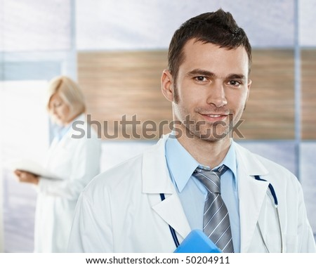 Medical team on hospital corridor mid-adult doctor in front looking at camera, smiling. - stock photo
