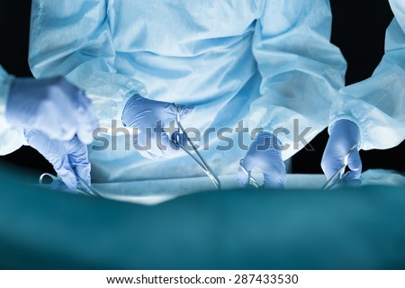 Medical team performing operation. Group of surgeon at work in operating theatre. Hands close-up view - stock photo