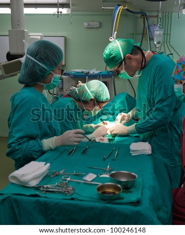 Medical team performing surgery on a young patient - stock photo