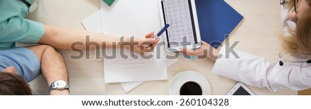 Medical team sitting at the table and analyzing cardiogram - stock photo