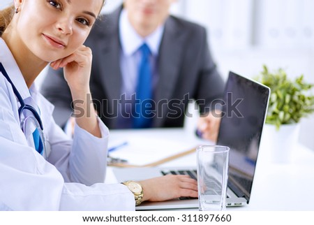 Medical team sitting at the table in modern hospital - stock photo