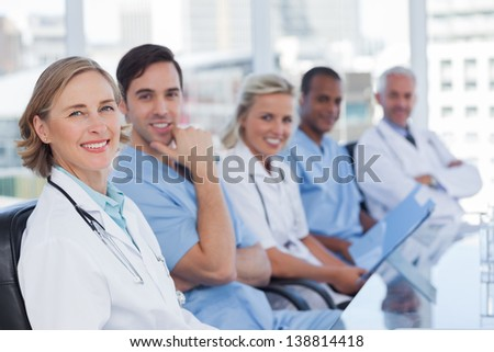 Medical team sitting in row and looking at the camera - stock photo
