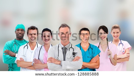 Medical team standing arms crossed in line on blurry background - stock photo