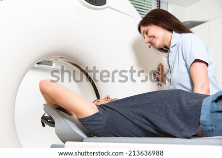 Medical technical assistant councelling patient and preparing scan of the spine with x-ray computed tomography CT  in radiology - stock photo