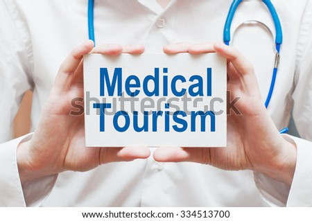 Medical Tourism card in hands of Medical Doctor - stock photo