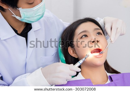 Medical treatment at the dentist office, Dentist and his assistant carrying out a thorough examination - stock photo