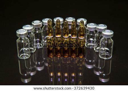 medical vials and syringe on black background - stock photo