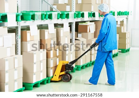 medical warehouse worker man loading boxes with medcine drugs by hand forklift  - stock photo