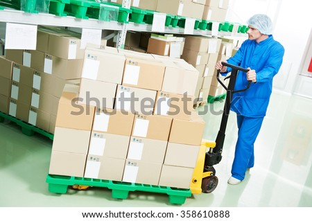 medical warehouse worker man loading boxes with medcine drugs by hand forklift at pharmacy factory  - stock photo