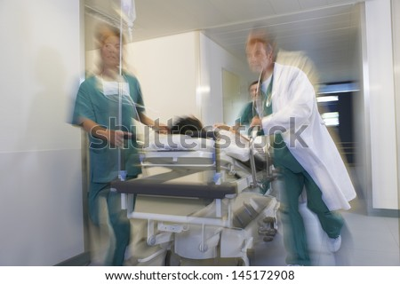 Medical workers moving patient on gurney through hospital corridor - stock photo