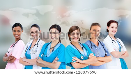 Medical workers standing against world map background - stock photo