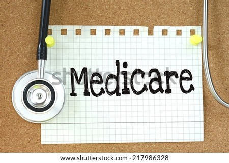 Medicare handwritten on paper note with stethoscope on wooden table - stock photo