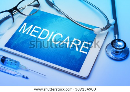 Medicare word on tablet screen with medical equipment on background - stock photo