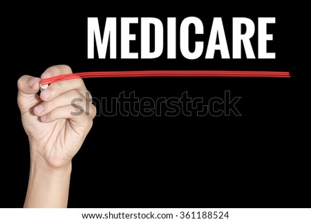 Medicare word writing by men hand holding red highlighter pen on dark background - stock photo