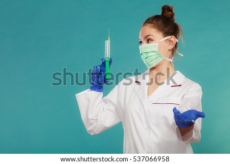 Medication and cure. Injection concept. Young woman doctor holding syringe. Female specialist with mask on face and vaccine in hand.