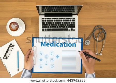 Medication Doctor writing medical records on a clipboard, medical equipment and desktop on background, top view, coffee - stock photo