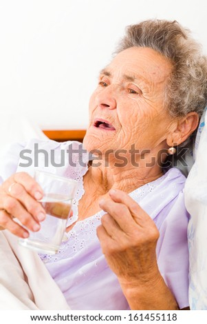 Medication given to elderly woman in bed. - stock photo
