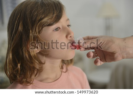 Medication: little girl taking cough syrup - stock photo