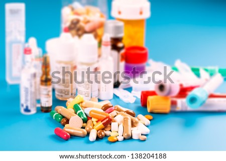 Medications tablets and capsules in a beaker - stock photo
