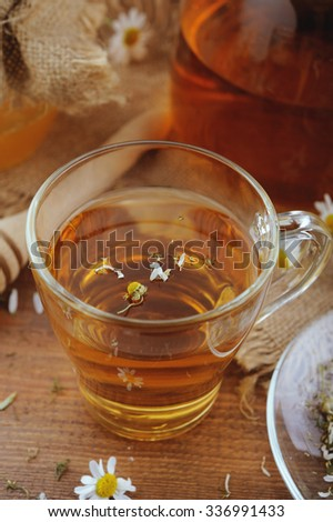 Medicinal flowers and herbal tea of chamomile with honey on rustic background