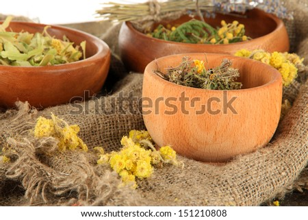 Medicinal Herbs in wooden bowls on bagging on table close-up - stock photo