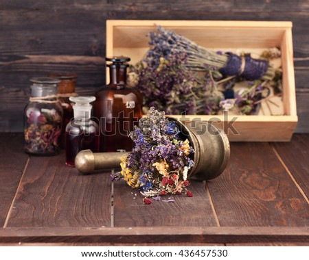 Medicinal herbs mortar and bottles tincture in a wooden box. Herbal medicine concept - stock photo