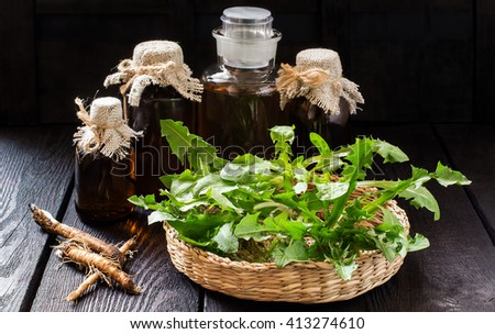 Medicinal plant - dandelion. Dandelion leaves in a basket, tincture and syrup in pharmaceutical bottles, roots on wooden background. It is used for herbal medicine and healthy food   - stock photo