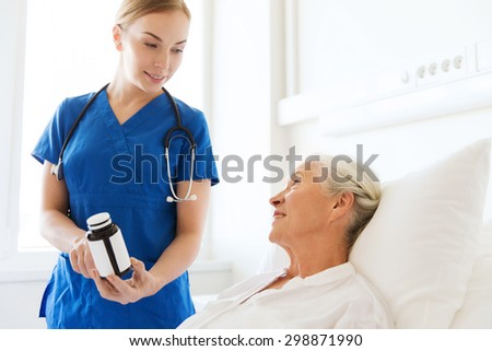 medicine, age, health care and people concept - doctor or nurse showing medicine to senior woman at hospital ward - stock photo