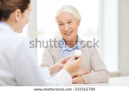 medicine, age, health care and people concept - doctor showing pills to happy senior woman at hospital - stock photo