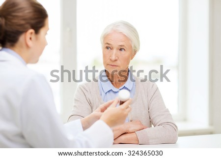 medicine, age, health care and people concept - doctor showing pills to senior woman at hospital - stock photo