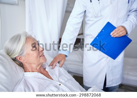 medicine, age, health care and people concept - doctor visiting happy senior woman at hospital - stock photo