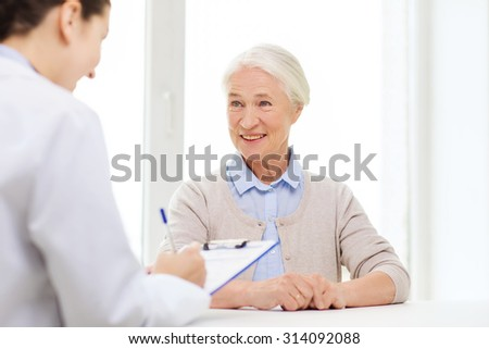 medicine, age, health care and people concept - doctor with clipboard writing prescription for senior woman at hospital - stock photo
