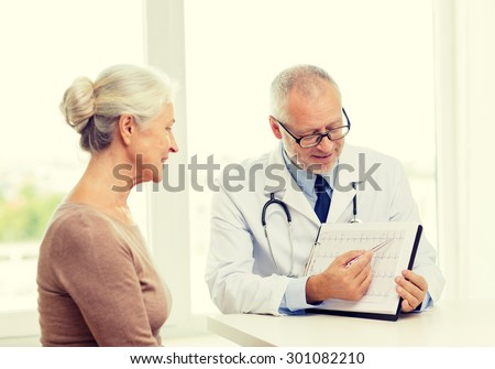 medicine, age, health care and people concept - smiling senior woman and doctor meeting in medical office - stock photo