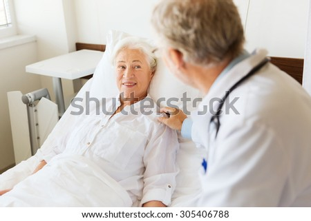 medicine, age, support, health care and people concept - doctor visiting and cheering senior woman lying in bed at hospital ward - stock photo